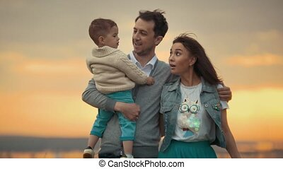 Young mom and dad walk with the child in nature and communicate, summer evening, sunset