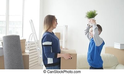 Young Mom and son are moving to a new apartment