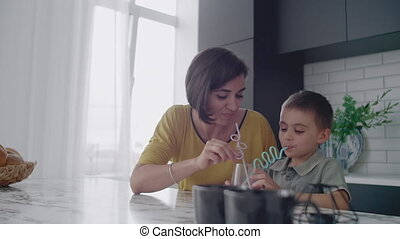 Young mom and son drinking juice with candy at kitchen. Happy mother spending time with son sitting on table in slow motion