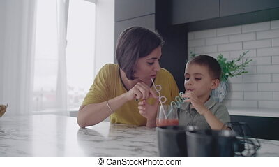 Young mom and son drinking juice with candy at kitchen....