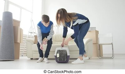 Young Mom and son with their cat are moving to a new apartment