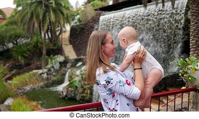 Young mom holding a baby playing with him smiling and laughing near the waterfall in the Park
