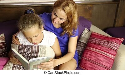 Young mom reading a book aloud to her daughter in the living room on the couch before sleeping
