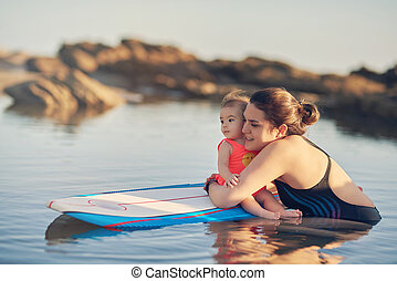 Young mom with baby on surf board
