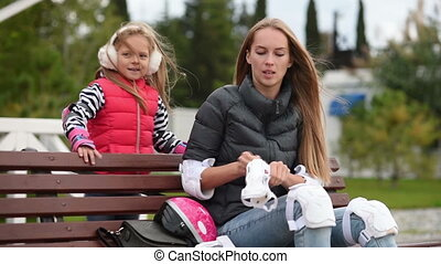 Young mom with her child rollerskating in park