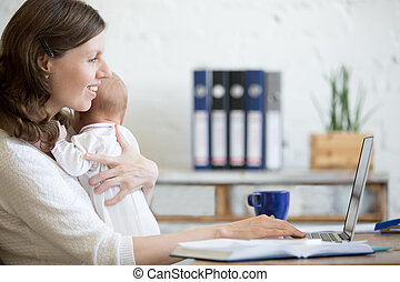 Young mom working with her baby in the office