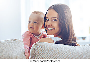 Young mommy. Rear view of cheerful beautiful young woman holding baby girl in her hands and looking at camera with smile while sitting on the couch at home