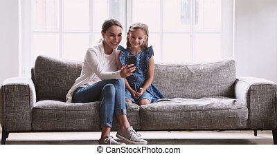 Young mommy showing funny video on cellphone to preschool girl.