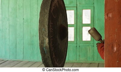 Young monk beats in big gong in nepalese village Lho, Nepal.