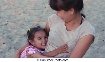 Young mother and baby daughter hugging on the beach.