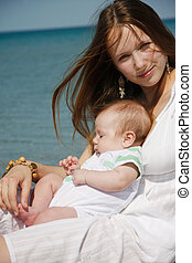 young mother and baby on sea background