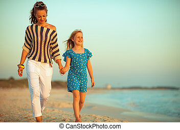 young mother and child on seacoast at sunset walking