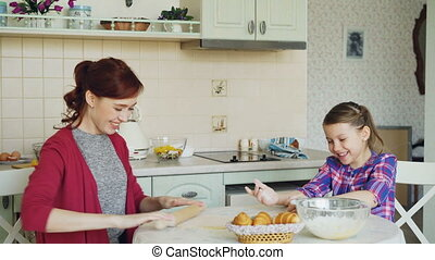 Young mother and cute daughter cooking together talking in...