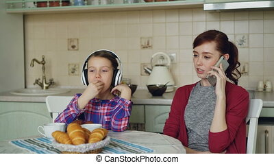 Young mother and cute daughter having breakfast in the morning in kitchen at home. Little girl listening music with headphones eating muffins while her busy mom talking by phone