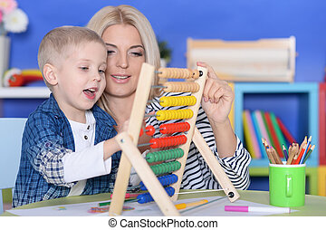 Young mother and cute little son with abacus