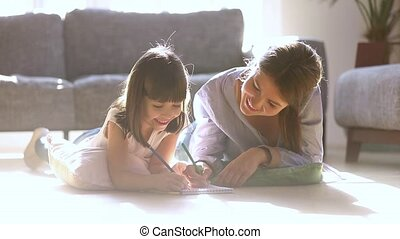 Young mother and daughter lying on warm floor drawing ...