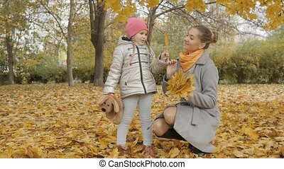 young mother and daughter playing in the park