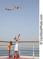 young mother and daughter playing with multicolored kite, standing on cruise liner deck