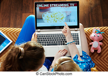 young mother and daughter using internet tv on laptop