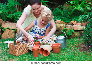 Young mother and daughter watering plants - Happy young...