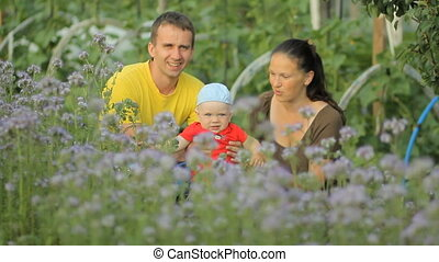 Young mother and father holding her newborn baby in a purple flower field