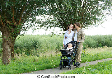Young mother and father walking outdoors with baby in pram