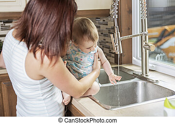 Young mother and her adorable toddler daughter in kitchen
