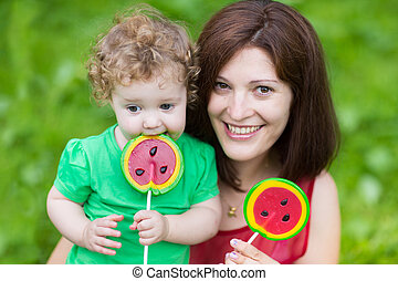 Young mother and her baby daughter eating watermelon candy ...