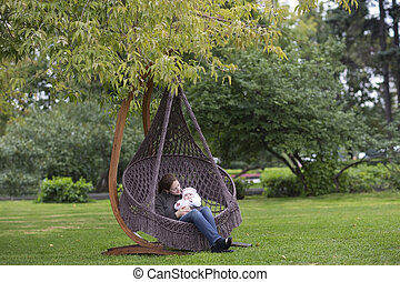 Young mother and her baby daughter relaxing in a hammock
