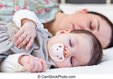 Young mother and her baby girl sleeping in the bed