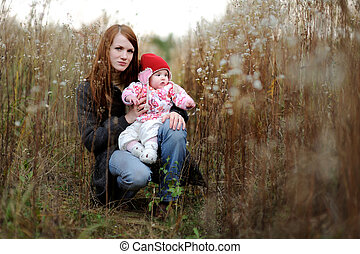 Young mother and her baby in a meadow