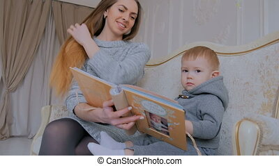 Young mother and her baby son looking photobook