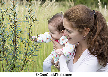 Young mother and her baby watching a caterpillar