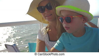 Young mother and her child are doing selfie on the boat. Little boy kisses mom on the cheek; they laugh and look happy