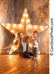 Young Mother and her Child Boy Having Fun with Wooden Plane Toy on Studio Background