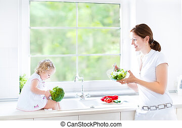 Young mother and her cute toddler daughter cooking together...