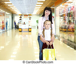 Young mother and her daughter doing shopping