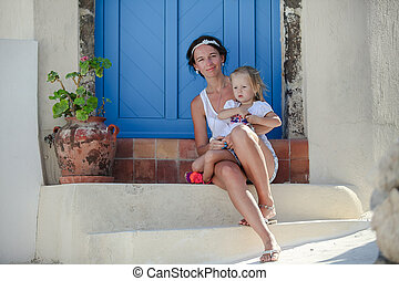 Young mother and her daughter sitting on doorstep of old...