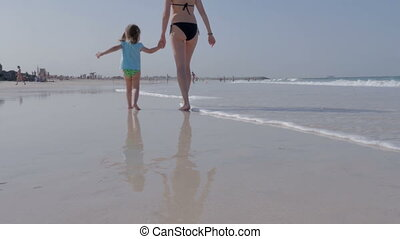 Young mother and her little daughter are walking with their hands on the beach.