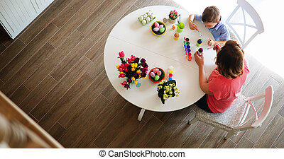 Young mother and her son having fun while painting eggs for Easter