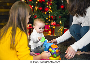 Young mother and her two children opening a Christmas presents by a Christmas tree in cozy living room