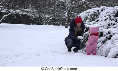 young mother and little baby girl have fun with snow. 4K
