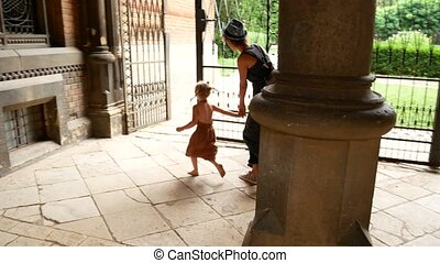 Young mother and little daughter are running among the...