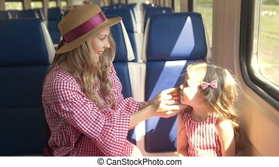 Young mother and little daughter playing patty-cake sitting in front of window in empty train