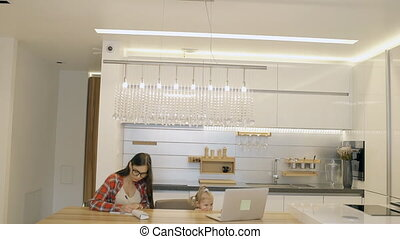 Young mother and little daughter spending time together in modern kitchen at home.