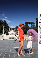 Young mother and little daughter standing on Piazza Popolo, nearh water flows from an ancient aqueduct Aqua Vergine, focus on mother