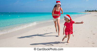 Young mother and little girl running at tropical beach -...