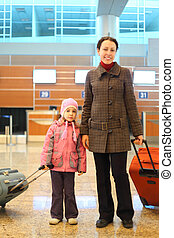 young mother and little girl with suitcases standing at airport focus on child
