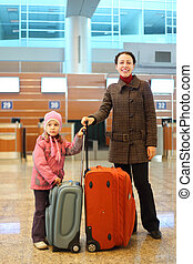 young mother and little girl with suitcases standing at airport