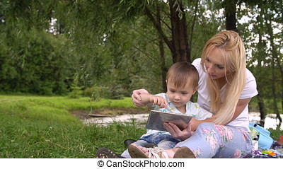 Young mother and little son spending day in the park. Woman and child using tablet computer.